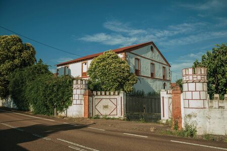 Countryside road on sunset with gate and charming cottage amidst lush green trees, near Elvas. A gracious star-shaped fortress city on the easternmost frontier of Portugal.