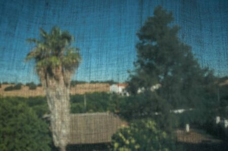 Curtain texture in front of countryside landscape with leafy trees and cottage, in a sunny day near Elvas. A gracious star-shaped fortress city on the easternmost frontier of Portugal.