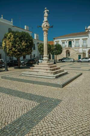 Marble pillory and sculpture on top in deserted square with old buildings, in a sunny day at Campo Maior. A cute little town with Roman, Moorish and medieval influences in eastern Portugal.