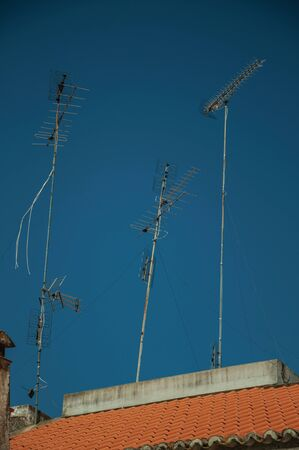 Set of television antennas on top of roof with blue sky in the background at Campo Maior. A cute little town with Roman, Moorish and medieval influences in eastern Portugal. Banco de Imagens