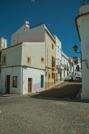 Old terraced houses with cracked plaster and deserted causeway in sunny day on a slope street of Campo Maior. A cute little town with Roman, Moorish and medieval influences in eastern Portugal.