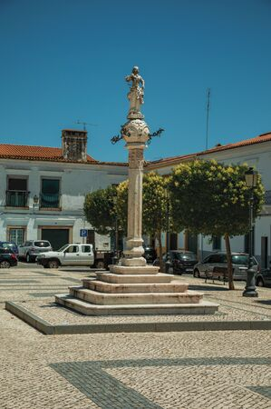 Marble pillory and sculpture on top in cobblestone square with old building, on sunny day at Campo Maior. A cute little town with Roman, Moorish and medieval influences in eastern Portugal.