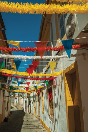 Deserted alley with festive colorful decoration and old terraced houses, on sunny day at Portalegre. A nice little town at the bottom of Mamede Mountain Range in eastern Portugal.
