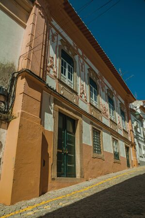 Old colorful mansion with exquisite plaster ornaments on the wall and deserted causeway, on sunny day at Portalegre. A nice little town at the bottom of Mamede Mountain Range in eastern Portugal.