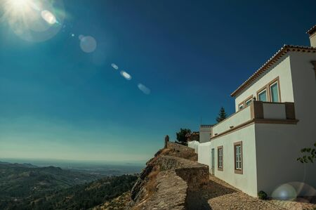 Old house and stone breastwork over ridge, with mountainous landscape on sunny day at Marvao. An amazing medieval fortified village perched on a granite crag in eastern Portugal. Retouched photo. Reklamní fotografie