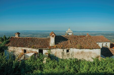 Old worn house and green bushes with landscape covered by trees and cultivated fields in a sunny day at Marvao. An amazing medieval fortified village perched on a granite crag in eastern Portugal.