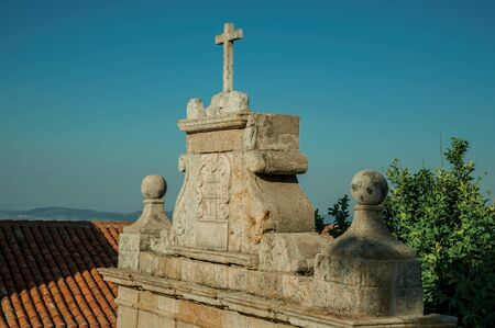 Cross over decorated baroque style wall with the city coat of arms carved in stone, in a sunny day at Marvao. An amazing medieval fortified village perched on a granite crag in eastern Portugal.