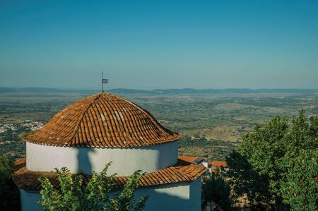 Rooftop in dome shape over rounded house next to trees, with rural landscape covered by fields on sunset at Marvao. An amazing medieval fortified village perched on a granite crag in eastern Portugal.