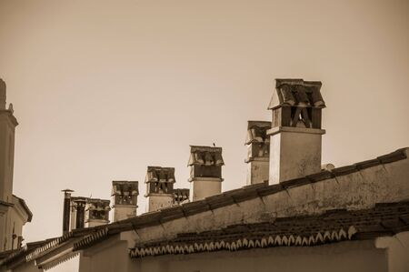 Several chimneys over rooftop of old house with worn plaster wall, at sunset in Marvao. An amazing medieval fortified village perched on a granite crag in eastern Portugal. Black and white photo. Banco de Imagens