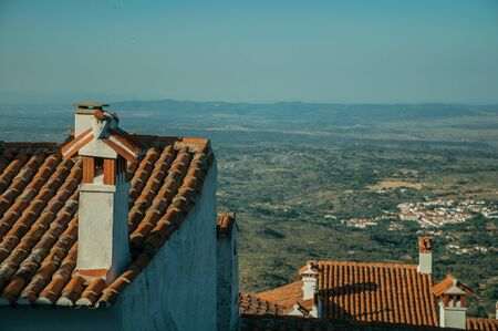 Several chimneys over rooftops of old house with landscape covered by trees and fields in a sunny day at Marvao. An amazing medieval fortified village perched on a granite crag in eastern Portugal. Reklamní fotografie