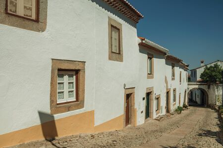 Charming facade of old houses with whitewashed wall in cobblestone alley on the way down, in a sunny day at Marvao. An amazing medieval fortified village perched on a granite crag in eastern Portugal.