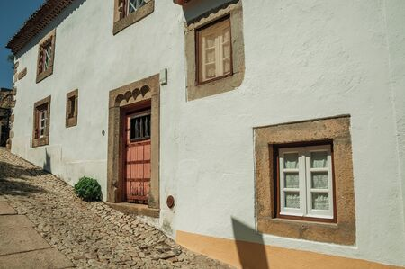 Charming facade of old house with whitewashed wall in cobblestone alley on the way down, in a sunny day at Marvao. An amazing medieval fortified village perched on a granite crag in eastern Portugal.