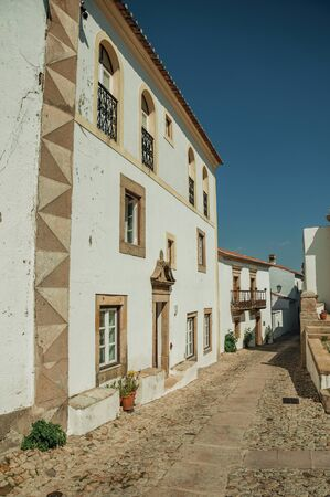 Baroque facade of old house with whitewashed wall and stone ornaments in a narrow alley, on sunny day at Marvao. An amazing medieval fortified village perched on a granite crag in eastern Portugal. Reklamní fotografie
