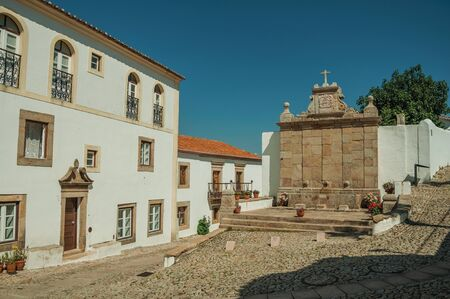 Charming old house and stone fountain in baroque style in front a little cobblestone square, in a sunny day at Marvao. An amazing medieval fortified village on a granite crag in eastern Portugal.