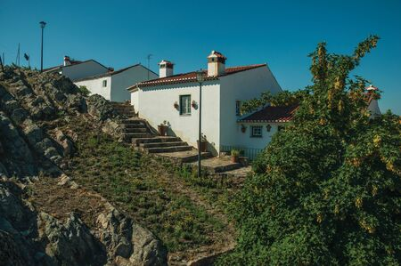 Old houses with whitewashed wall over rocky ridge, with stairs and leafy trees in a sunny day at Marvao. An amazing medieval fortified village perched on a granite crag in eastern Portugal. Reklamní fotografie