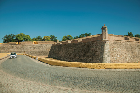 Deserted street with car next to the city wall corner with watchtower and dry moat, in a sunny day at Elvas. A gracious star-shaped fortress city on the easternmost frontier of Portugal. Editorial