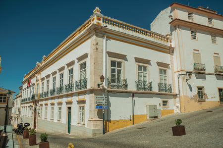 Corner of colorful house with big windows and iron balconies on a deserted square in a sunny day at Elvas. A gracious star-shaped fortress city on the easternmost frontier of Portugal. Editorial
