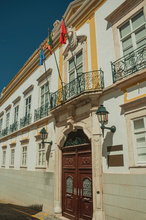 Facade of building with wooden gate, windows with decorated iron balustrade and flags in a sunny day at Elvas. A gracious star-shaped fortress city on the easternmost frontier of Portugal. Editorial