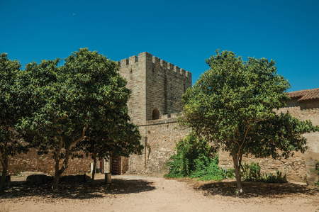 Stone walls and tower with merlons around central courtyard with green trees in a sunny day at the Castle of Elvas. A gracious star-shaped fortress city on the easternmost frontier of Portugal. Editorial