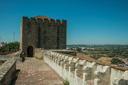 Pathway on top of thick stone wall with tower and merlons in sunny day at the Castle of Elvas. A gracious star-shaped fortress city on the easternmost frontier of Portugal.
