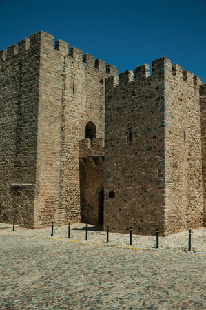 Stone walls and towers with merlons on a sunny day, in the front facade of the Elvas Castle. A gracious star-shaped fortress city on the easternmost frontier of Portugal. Editorial