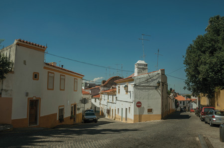 Elvas, Portugal - July 07, 2018. Old colorful terraced houses in front of deserted street with parked cars at Elvas. A gracious star-shaped fortress city on the easternmost frontier of Portugal. Redactioneel