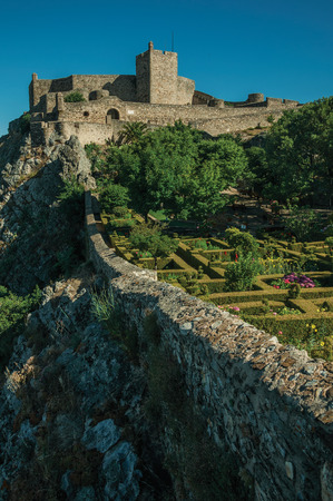 Stone walls and tower of Castle over rocky cliff in a sunny day, with lush flowered garden in the bottom at Marvao. An amazing medieval fortified village perched on a granite crag in eastern Portugal.
