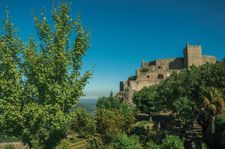 Stone walls and tower of Castle over rocky cliff in a sunny day, with lush wooden garden in the bottom at Marvao. An amazing medieval fortified village perched on a granite crag in eastern Portugal. Editorial