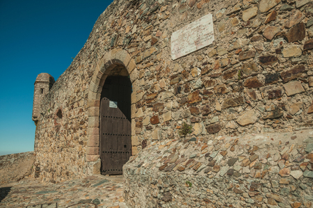 Marvao, Portugal - July 09, 2018. Gateway in the stone outer wall with door and watchtower at the Marvao Castle. An amazing medieval fortified village perched on a granite crag in eastern Portugal.