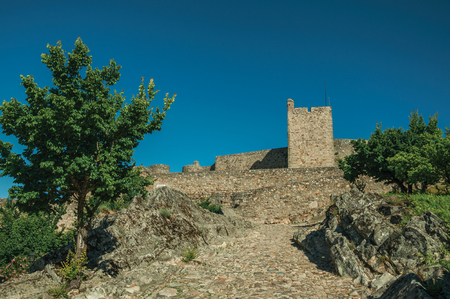 Cobblestone sidewalk on sunny day going up the slope towards stone wall and tower of Marvao Castle. An amazing medieval fortified village perched on a granite crag in eastern Portugal.