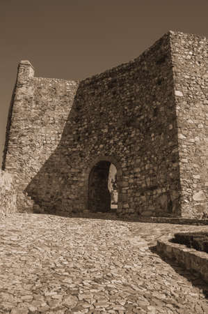 Arched gateway in the stone internal wall, on sunny day at the Marvao Castle. An amazing medieval fortified village perched on a granite crag in eastern Portugal. Black and white photo.