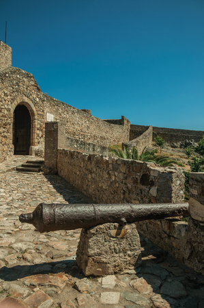 Close-up of old iron cannon next to gateway in the stone outer wall, in a sunny day at the Marvao Castle. An amazing medieval fortified village perched on a granite crag in eastern Portugal.