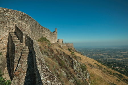 Stone outer walls and towers over rocky hill with countryside landscape, in a sunny day at the Marvao Castle. An amazing medieval fortified village perched on a granite crag in eastern Portugal. Editorial