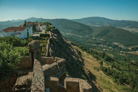 Old houses and church on top of ridge with stone wall and mountainous landscape, as seen from the Marvao Castle. An amazing medieval fortified village perched on a granite crag in eastern Portugal.