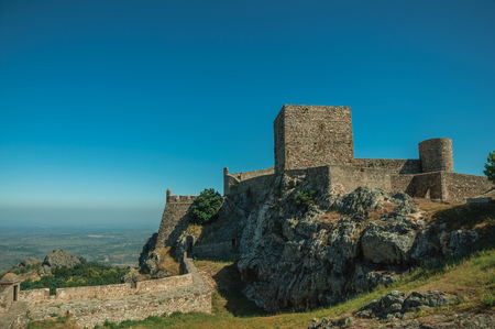 Stone walls and towers over rocky hill with lawn garden and countryside landscape, in a sunny day at Marvao Castle. An amazing medieval fortified village perched on a granite crag in eastern Portugal. Editorial
