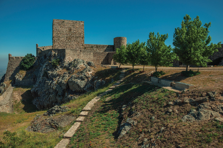 Stone walls and towers over rocky hill close to lawn garden with trees, in a sunny day at Castle of Marvao. An amazing medieval fortified village perched on a granite crag in eastern Portugal. Editorial