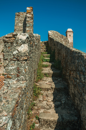Pathway with stairs on top of thick stone wall going up to small watchtower, in a sunny day at the Marvao Castle. An amazing medieval fortified village perched on a granite crag in eastern Portugal.