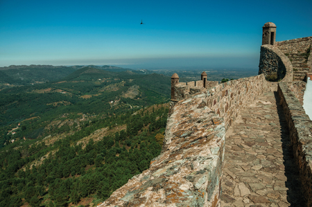 Pathway and stairs on top of thick stone wall with watchtowers over countryside landscape at the Marvao Castle. An amazing medieval fortified village perched on a granite crag in eastern Portugal. Editorial