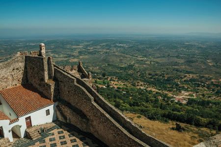 House and courtyard encircled by thick stone wall and countryside landscape, in a sunny day at the Marvao Castle. An amazing medieval fortified village perched on a granite crag in eastern Portugal. Editorial