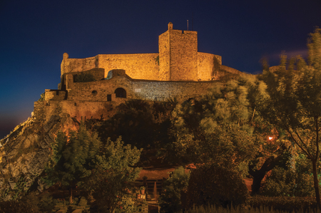 Stone walls and square tower of Castle over rocky cliff, with lush wooden garden in the bottom at dusk in Marvao. An amazing medieval fortified village perched on a granite crag in eastern Portugal.