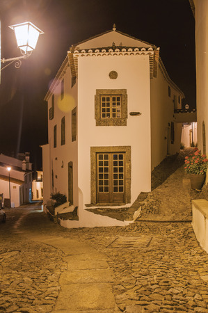 Charming facade of old corner house in between two cobblestone alleys on slope, at dusk in Marvao. An amazing medieval fortified village perched on a granite crag in eastern Portugal.