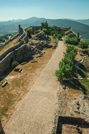 Pathway in the central courtyard encircled by thick stone wall, over hilly landscape at the Marvao Castle. An amazing medieval fortified village perched on a granite crag in eastern Portugal. Editorial