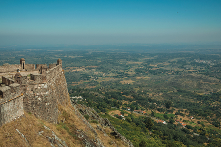 Stone walls and watchtowers in stronghold over cliff next to Castle, with hilly landscape in a sunny day at Marvao. An amazing medieval fortified village perched on a granite crag in eastern Portugal.