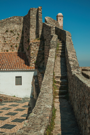Pathway and stairs on top of thick stone wall and watchtowers over countryside landscape at the Marvao Castle. An amazing medieval fortified village perched on a granite crag in eastern Portugal.