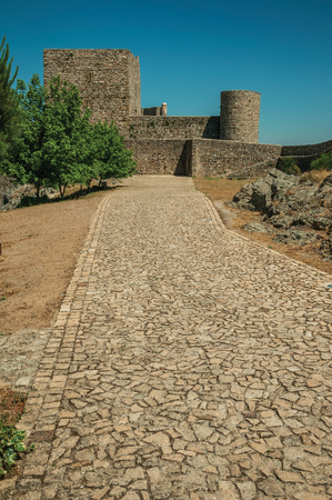 Cobblestone pathway going to thick solid walls and square tower, in a sunny day at the Marvao Castle. An amazing medieval fortified village perched on a granite crag in eastern Portugal.