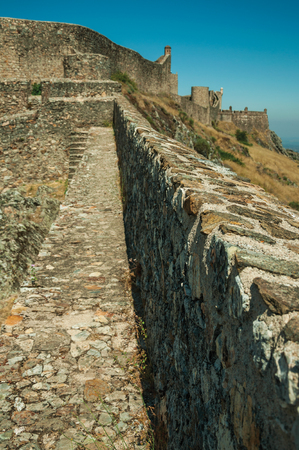 Close-up of pathway on thick stone wall and square tower over rocky hill, in a sunny day at the Marvao Castle. An amazing medieval fortified village perched on a granite crag in eastern Portugal. Editorial