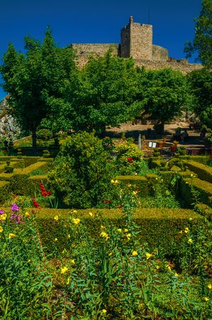 Stone walls and square tower of Castle over hill on sunny day, with flowered garden at Marvao. An amazing medieval fortified village perched on a granite crag in eastern Portugal. Retouched photo.
