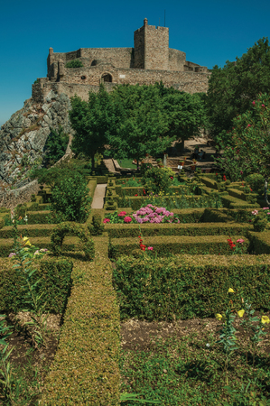 Stone walls and square tower of Castle over hill on sunny day, with lush wooden garden in the bottom at Marvao. An amazing medieval fortified village perched on a granite crag in eastern Portugal.