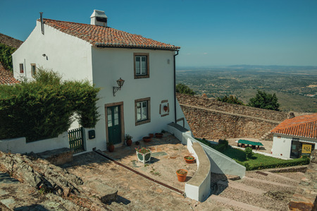 Marvao, Portugal - July 09, 2018. Old white house with countryside landscape in background, in a sunny day at Marvao. An amazing medieval fortified village on a granite crag in eastern Portugal. Editorial