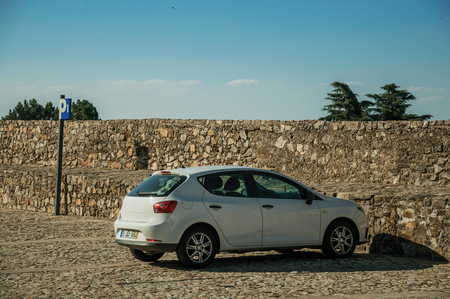 Marvao, Portugal - July 09, 2018. Car parked in front of wall made of rough stones with small watchtower in Marvao. An amazing medieval fortified village perched on a granite crag in eastern Portugal. Editorial
